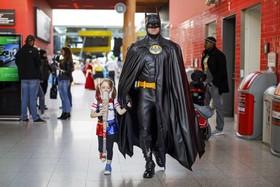 پدری با دخترش در حال حرکت به مراسم شخصیت های فیلم های کمیک در یک مرکز فروشگاهی در لندن انگلیس