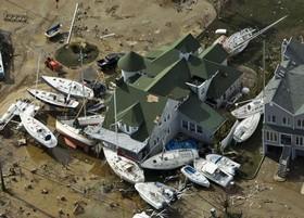 انتقال قایقها از کنار ساحل به میان شهر در کنار خانه ای در نیوجرسی در جریان توفان سندی