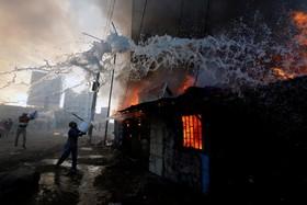 تلاش مردم برای خاموش کردن آتش سوزی عمدی در یک محله زاغه نشین در نایروبی کنیا