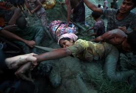 کمک عکاس ها به یک آواره روهینگیا در رودخانه نف در نزدیکی مرز میانمار و بنگلادش