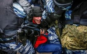 نیروهای ضد شورش در مسکو یک تظاهرکننده را که در روز اتحاد تظاهرات کرند دستگیر میکند