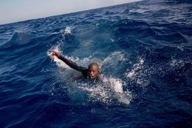 دریای مدیترانه و یک مهاجر غیرقانونی که تلاش می کند جانش را با نزدیک شدن به یک قایق نجات از مرگ برهاند