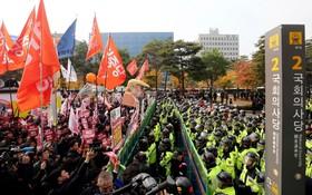 تظاهرکنندگان مخالف دونالد ترامپ و دیدارش از سئول کره جنوبی در مقابل پلیس ضد شورش