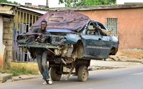 جوانی در آبیجان در ساحل عاج در حال حمل بدنه یک خودرو با گاری برای بازیافت