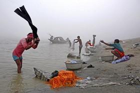 مردم در حال شستن رخت و لباس در کنار رودخانه براهماپوترا در هند