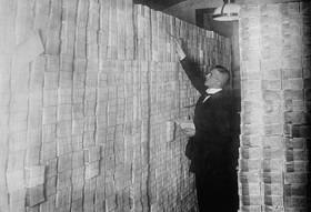 بانكدار برلين در حال چيدمان پول هاي بسته بندي شده.jpg