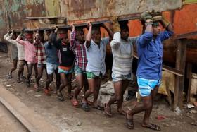 کارگران در بنگلادش در حال حمل یک قطع آهنی