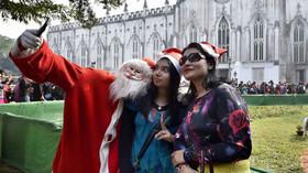 شخصی که لباس بابانوئل پوشیده و عکس سلفی می گیرید.