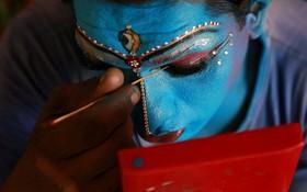 مردی در حال آرایش چهره برای شرکت در مراسم سال نو در کرلای هند