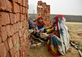 زنان کارگر هندی در سرما در حال گرم کردن خویش در ساختمان محل کارشان هستند