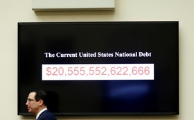 استیون منوچین وزیرخزانه داری آمریکا در حال عبور از مقابل تابلویی که میزان بدهی دولت آمریکا را نمایش می دهد