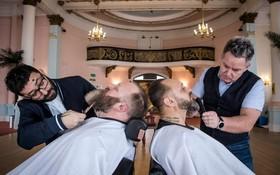 دو هنرمند آرایشگر در حال پیرایش ریش دو شرکت کننده در مسابقه ریش در انگلیس
