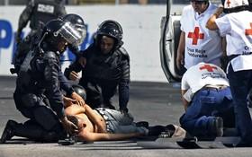 کمک پلیس ضد شورش و نیروهای امداد به یک تماشاگر در بازی فوتبال در هندوراس