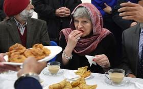 ترزا می در کنار سیک های انگلیسی در حال خوردن سمبوسه