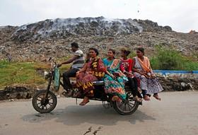 زباله های در حال سوختن و خانواده ای که با متور عبور می کنند در هند