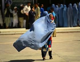 زن افغانستانی به همراه کودکش برای دریافت کمک غذایی به مرکز خیریهای در شهر هرات میرود