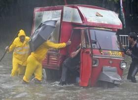 نیروهای امداد رسان هندی در حال نجات خودروی گرفتار شده در سیلاب ناشی از بارانهای موسمی بمبئی