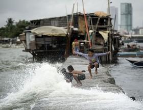 بازی کودکان فیلیپینی در کنار امواج ناشی از باران در منطقه گرمسیری مانیل