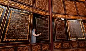 موزه قرآن در پالم بانگ در اندونزی و بخشی از صفحه های قرآن کریم که بر روی  چوب کنده کاری شده است