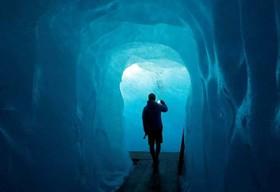 """یک گردشگر در حال بازدید از یک غار یخی در """"فورکا"""" سوییس"""