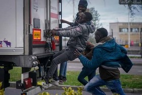 پناهجویان آفریقایی در تلاش برای سوار شدن به یک کامیون در مرز فرانسه و بریتانیا