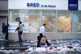 نصب حفاظ برای شیشه های یک بانک از بیم آشوب های خیابانی در شهر پاریس