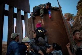 تلاش مهاجران هندوراسی برای عبور از مانع مرزی بین مکزیک و ایالات متحده آمریکا/