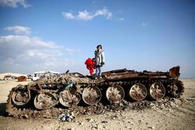 عکس یادگاری دختر 11 ساله سوری روی یک تانک تخریب شده در شمال حلب و در منطقه مرزی سوریه و ترکیه