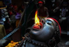 """مرد هندو در لباس خدای """"شیوا"""" در حال اجرای آتشبازی در جشنوارهای در اللهآباد هندوستان"""