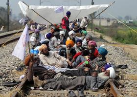 """کشاورزان هندی در اعتراض به سیاستهای اقتصادی دولت هند در روستایی در ایالت """" آمریتسار"""" مسیر عبور قطار را بسته اند. در اثر این اعتراض 22 قطار حرکت خود را متوقف کرده و 24 قطار تغییر مسیر دادند."""