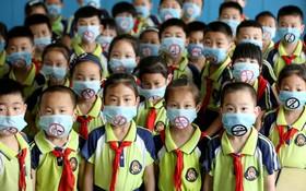 (تصاویر)  دانش آموزان در منطقه شاندونگ چین با ماسک هایی با علامت سیگار ممنوع در روز جهانی دخانیات ممنوع