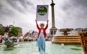 (تصاویر) در میان تظاهرکنندگان علیه سفر دونالد ترامپ به انگلیس در میدان ترافالگار در لندن زنی با لباس شبیه به مجسمه آزادی پلاکارد نه به جنگ با ایران را در دست دارد