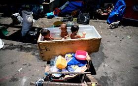 (تصاویر)  حمام کودکان در یخچال اوراق در مانیل فلیپین