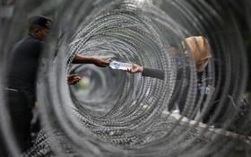 (تصاویر) پلیسی از دستفروشی از میان سیم خارداردر دادگاه قانون اساسی اندونزی آب خریداری می کند