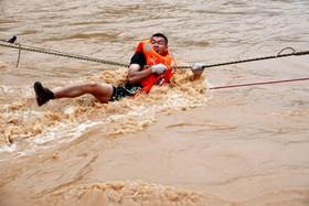 (تصاویر) یک امدادگر چینی در حال تلاش برای نجات گرفتارشدگان در روستایی در گوانگ دونگ