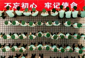 (تصاویر) اعضای نیروهای شبهه نظامی چین درسالگرد تشکیل حزب کمونیست در نودو هشتادومین سال اسامی خودرا روی یک تابلو تبلیغاتی ثبت می کنند