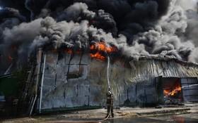 (تصاویر) تلاش آتش نشانان برای خاموش کردن آتش سوزی در یک انبار در کورنسکایا در اوکراین