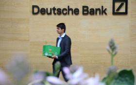 (تصاویر) بنای بانک آلمان در انگلیس که مردی با جعبه وسایلش این ساختمان را ترک می کند مقامات این بانک اعلام کردند که برای کاهش هزینه بزودی هجده هزار شاغل را از این بانک اخراج می کنند