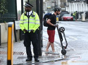 (تصاویر) مردی با موتور برقی خود در حال عبور است که توسط پلیس به دلیل غیرقانونی بودن تردد این نوع موتور در خیابان های لندن متوقف شده است