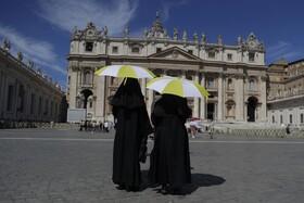 (تصاویر) دو مادر روحانی در میدان سنت پیتر واتیکان با چتری که از گرما برسر گرفته اند در انتظار دعای هفتگی پاپ هستند