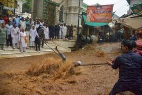 (تصاویر) عبور مردم از خیابانی در اجمر هند پس از بارندگی شدید و سیل در خیابان ها