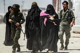 (تصاویر) ماموران امنیتی در سوریه گروهی از زنان را که گفته می شود از وابستگان گروه تروریستی داعش هستند به اردوگاه زندانیان  انتقال می دهند