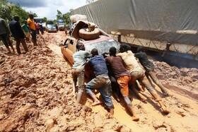 (تصاویر) مردان خودرویی را که در جاده ای در لیبریا به دلیل بارندگی در گل مانده هل می دهند جاده ها در این کشور نامناسب است و جوج وآ فوتبالیست سابق و رئیس جمهورکنونی لیبریا غول داده که جاده ها را اصلاح کند