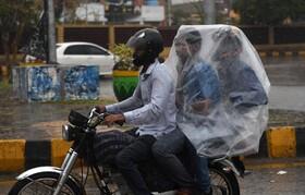 (تصاویر) مسافرکشی با موتور در کراچی پاکستان هنگام بارندگی