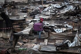 (تصاویر) یک ساکن شرک زاغه نشینی در کیپ تاون در آفریقای پس از آتش سوزی وسایل باقی مانده را جمع آوری کرده است