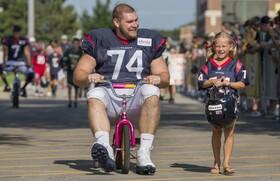 (تصاویر) هیوستون تگزاس پیش از بازی فوتبال آمریکایی یکی از بازیکنان در حال دوچرخه سواری در کنار یک کودک