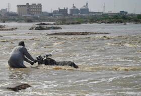 (تصاویر)تلاش مردی برای نجات موتورش در سیل در کراچی پاکستان