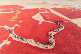 (تصاویر) تماشاچیان در منطقه گنسو در چین از طرحی از نقشه چین و پرچم این کشور که با فلفل های خشگ ساخته شده عبور می کنند