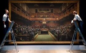 (تصاویر) حراج تابلویی از بنکسی در انگلیس که مجلس عوام انگلیس را نشان می دهد که میمون ها بر کرسی های آن نشسته اند