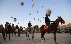 (تصاویر) سوارکاری جهانگردان در آسمان پر از بالن های هوای داغ در کاپادوکیای ترکیه